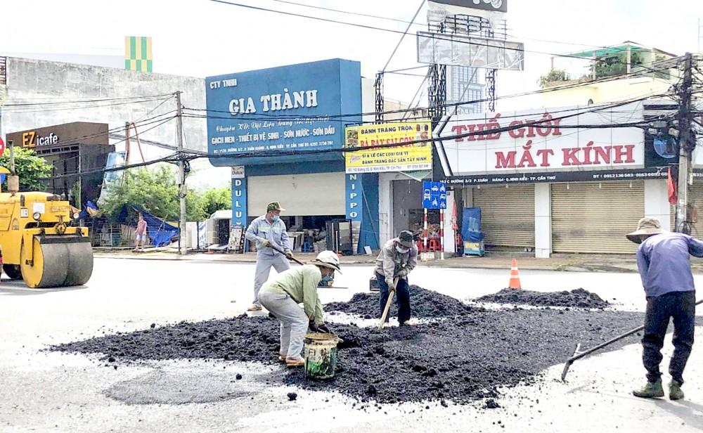 Công nhân đang giặm vá mặt đường hư hỏng tại giao lộ đường 3 Tháng 2 với đường Trần Ngọc Quế.