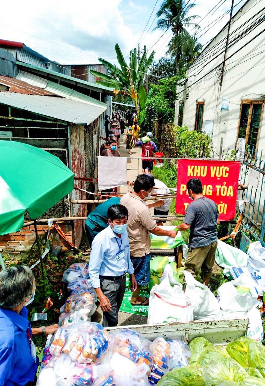 Các lực lượng chức năng của phường Hưng Thạnh tổ chức cấp phát lương thực, nhu yếu phẩm vào khu phong tỏa cho người dân. Ảnh: CTV