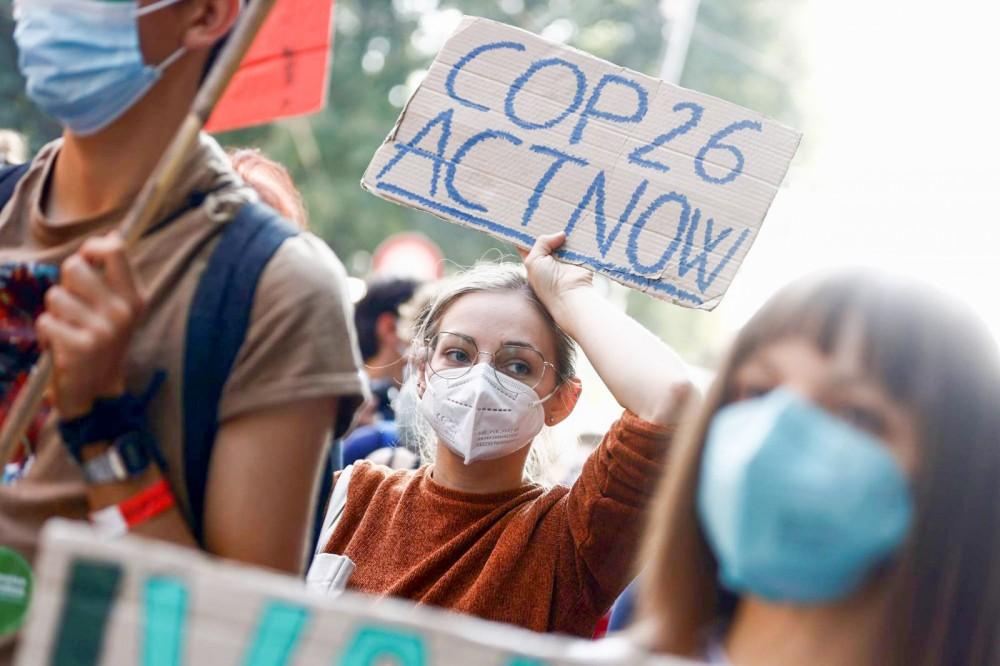 Các bạn trẻ tuần hành kêu gọi hành động tại Hội nghị COP26. Ảnh: Reuters