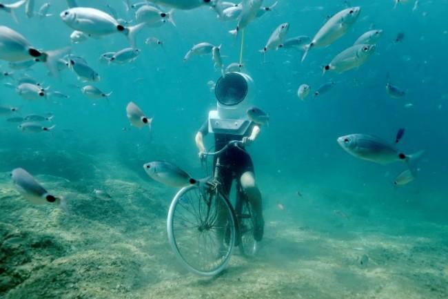 Một nữ du khách đang lặn xuống biển và giả vờ đạp xe đạp ở Công viên dưới nước tại Pula, Croatia, hôm 1-8. Ảnh: Reuters.