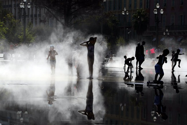 Trẻ em Pháp chơi đùa trong hơi nước ở một vòi phun nước khi thành phố Nice gặp đợt nóng bức, hôm 2-8. Ảnh: Reuters.