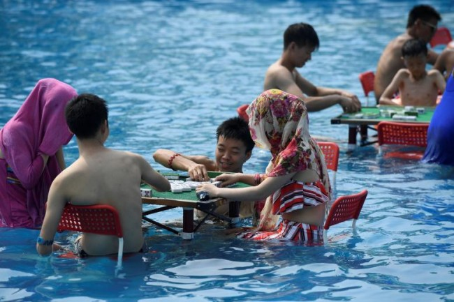 Người dân Trung Quốc chơi cờ mạt chược dưới nước tại một công viên nước trong một ngày nóng bức ở Trùng Khánh, hôm 2-8. Ảnh: Reuters