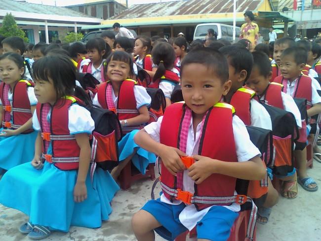 Trẻ em (huyện Cờ Đỏ) vui mừng được tặng áo phao, phòng ngừa rủi ro tai nạn đuối nước khi lũ về.