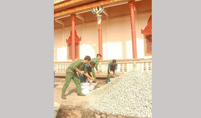 Cán bộ, chiến sĩ lực lượng vũ trang tham gia xây dựng sân chùa MuniutDom RăngSây. Ảnh: PHẠM TRUNG
