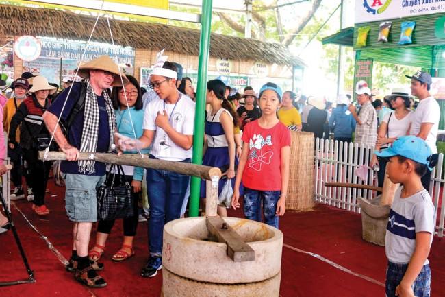 Du khách quốc tế thích thú với khu trưng bày và trải nghiệm làm bánh Nam bộ.