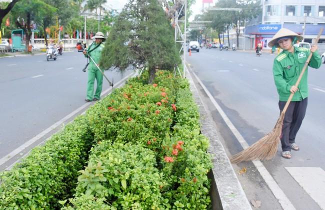 Công nhân Công ty TNHH môi trường xanh chi nhánh Cần Thơ cắt tỉa cây xanh, quét dọn, thu gom rác trên đường  Hòa Bình, quận Ninh Kiều, góp phần giữ cho tuyến đường xanh, sạch, đẹp trước, trong và sau lễ.