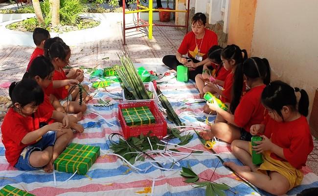 Trẻ Trường Mầm non Thị trấn Phong Điền gói bánh tét trong Hội chợ Mùa Xuân